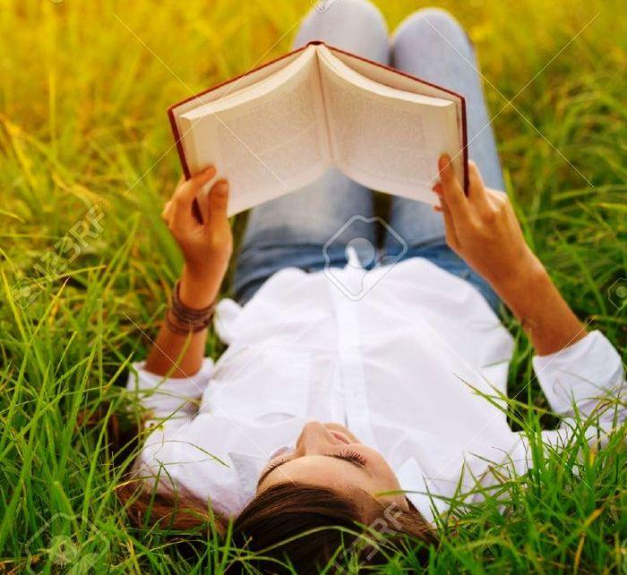 48345002-giovane-donna-che-gode-di-un-libro-di-lettura-esterna